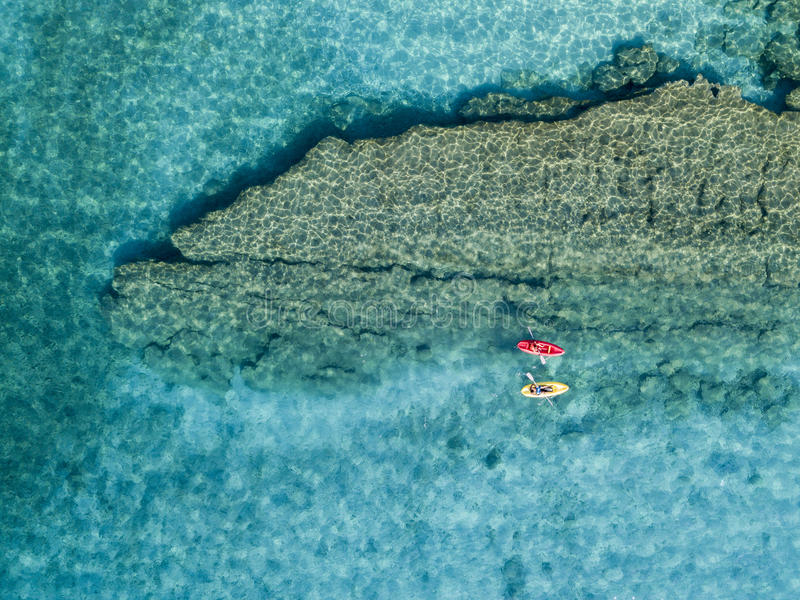 Aerial view of a canoe in the water floating on a transparent sea. Bathers at sea. Zambrone, Calabria, Italy royalty free stock photo