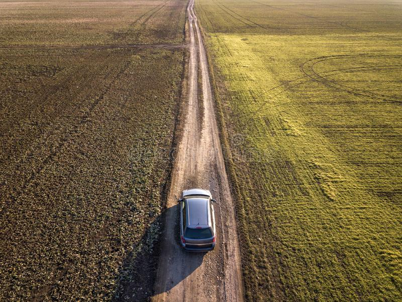 Aerial view of car driving by straight ground road through green fields on sunny blue sky copy space background. Drone photography.  stock photo