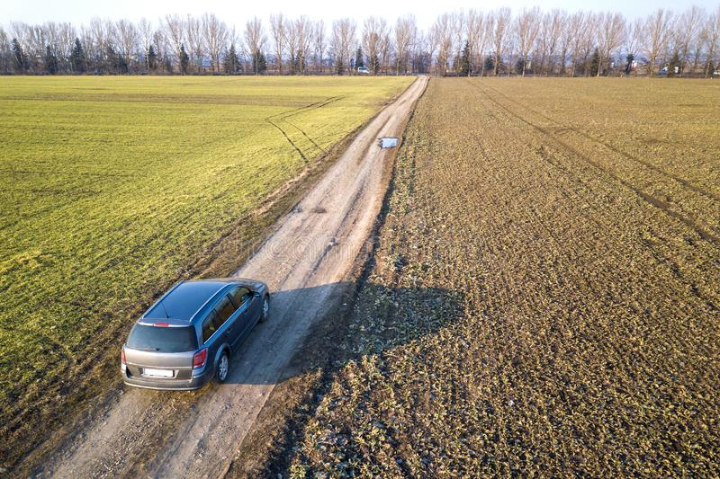 Aerial view of car driving by straight ground road through green. Fields on sunny blue sky copy space background. Drone photography royalty free stock photos