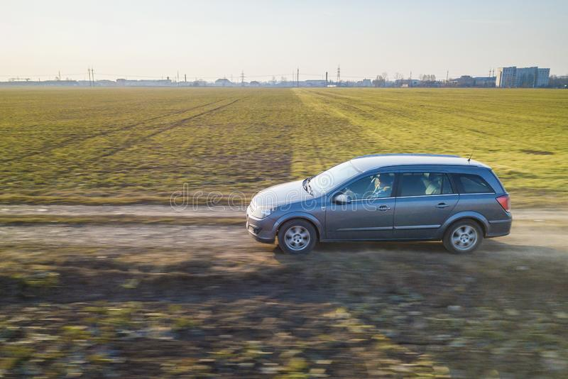 Aerial view of car driving by straight ground road through green fields on sunny blue sky copy space background. Drone photography.  stock images