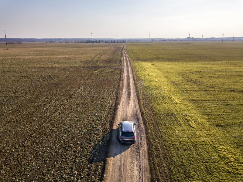 Aerial view of car driving by straight ground road through green fields on sunny blue sky copy space background. Drone photography.  royalty free stock images