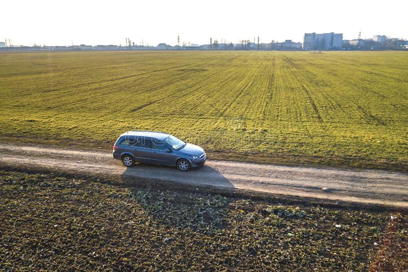 Aerial view of car driving by straight ground road through green. Fields on sunny blue sky copy space background. Drone photography royalty free stock images