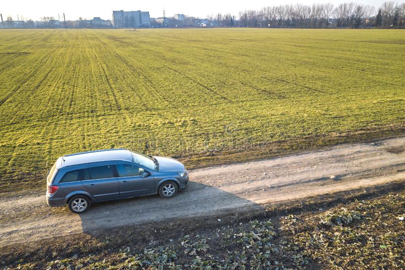 Aerial view of car driving by straight ground road through green fields on sunny blue sky copy space background. Drone photography.  stock image