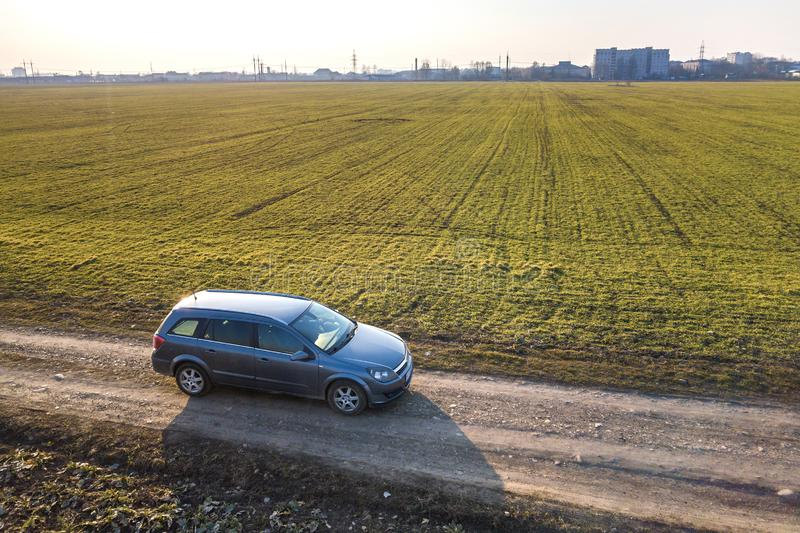 Aerial view of car driving by straight ground road through green. Fields on sunny blue sky copy space background. Drone photography stock image