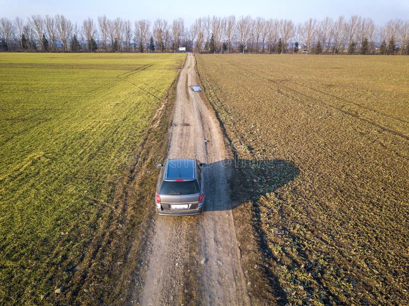 Aerial view of car driving by straight ground road through green. Fields on sunny blue sky copy space background. Drone photography royalty free stock image
