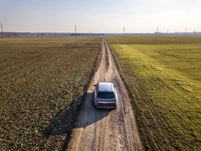 Aerial view of car driving by straight ground road through green fields on sunny blue sky copy space background. Drone photography.  royalty free stock photo