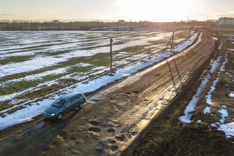 Aerial view of car moving along muddy rural road in bad condition on sunny spring or winter day.  stock photos