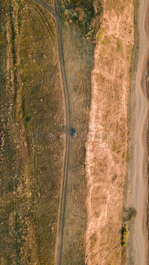Aerial view of a car parked near a rural road at sunset on the beach. Beautiful landscape with empty rural road. Top view from flying drone. Flat lay. Nature royalty free stock images