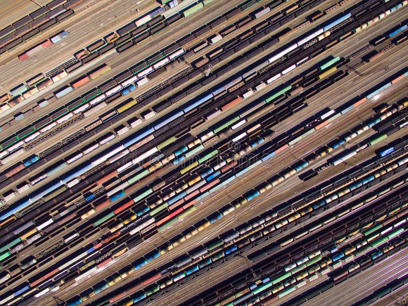 Aerial view of cargo trains. Railway wagons with goods on railroad. Top view of colorful freight train on the railway station royalty free stock photography
