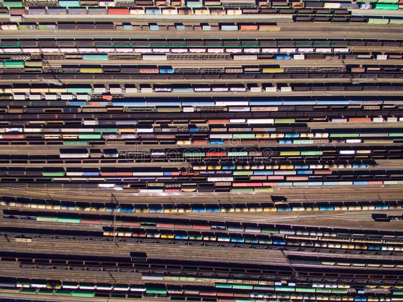 Aerial view of cargo trains. Railway wagons with goods on railroad. Top view of colorful freight train on the railway station royalty free stock image