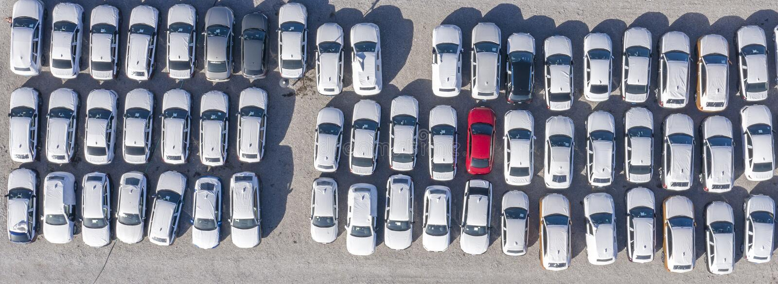 Aerial view cars for sale stock lot row, Car Dealer Inventory, parking lot. One red and all white stock images