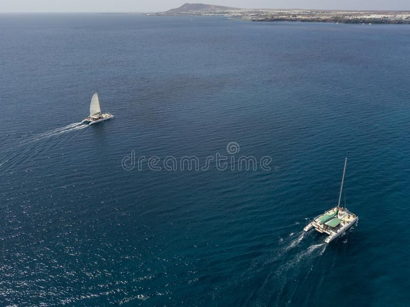 Aerial view of a catamaran crossing the ocean waters. Lanzarote, Canaries, Spain. Aerial view of a catamaran crossing the ocean waters, near the shores of the stock photography