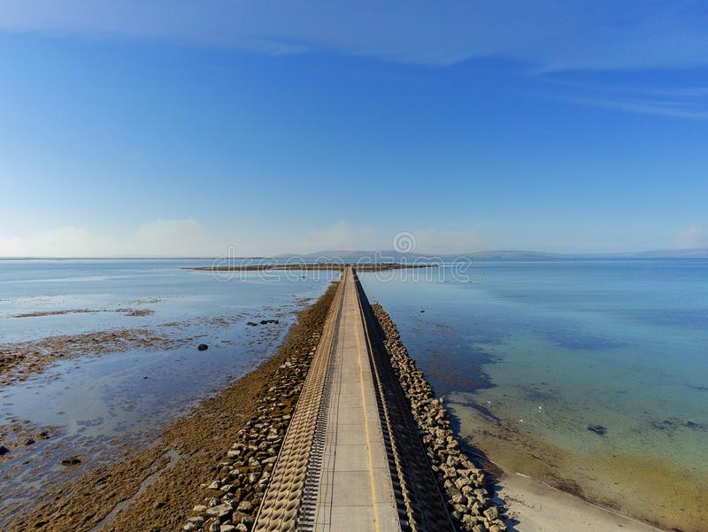 Aerial view. Causeway connecting Mutton island with Galway city. Warm sunny day, Blue sky and Atlantic ocean`s water stock images