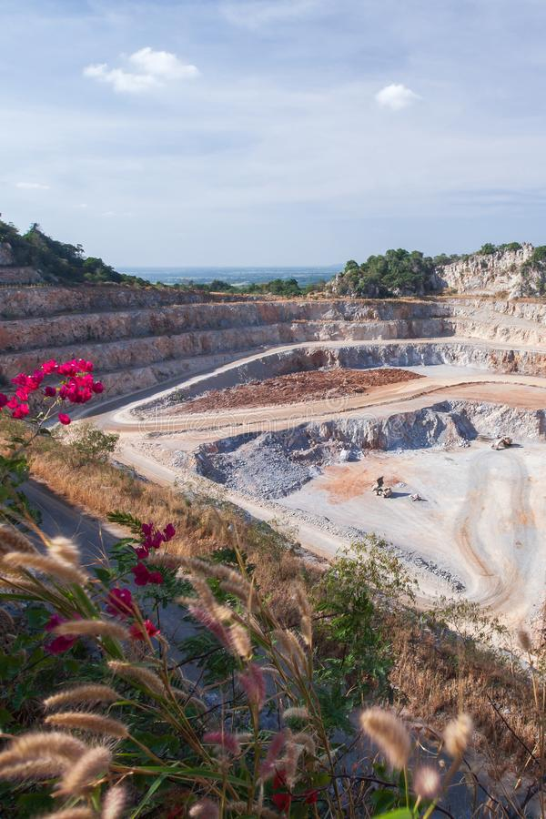 Aerial view of cement mining quarry with machinery at work. Fantastic landscape of open pit and limestone layers in rocks. Beautiful wild flowers at mine site stock photo