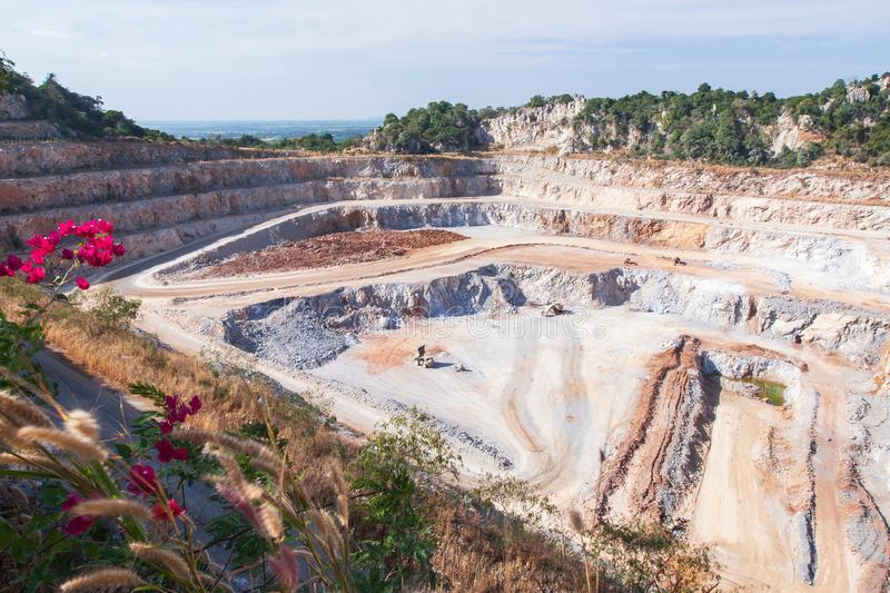 Aerial view of cement mining quarry with machinery at work. Fantastic landscape of open pit and limestone layers in rocks. Beautiful wild flowers at mine site stock photography