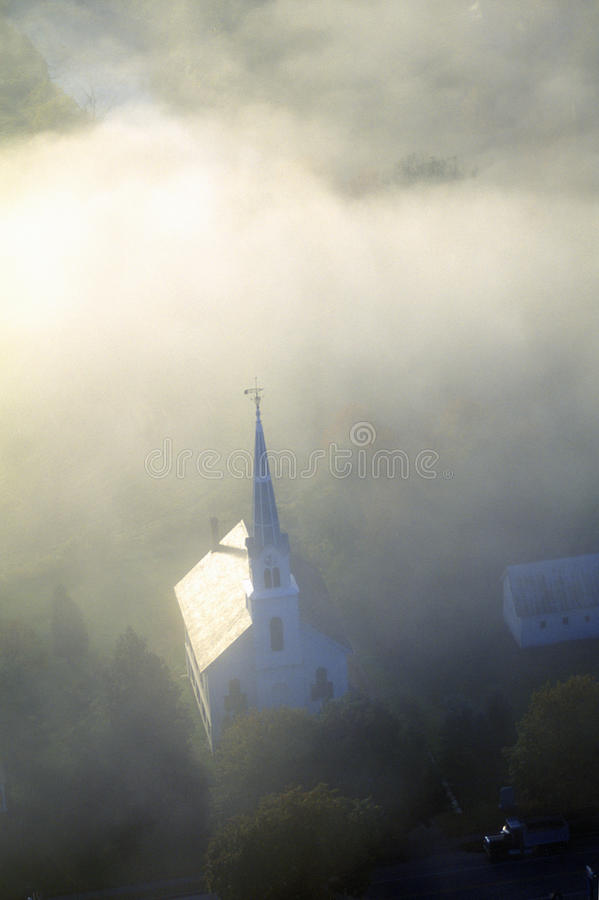 Aerial view of church steeple wreathed in morning fog in autumn, Waitsfield, VT stock photos
