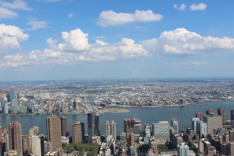 Aerial View of City Buildings by River Under Blue Cloudy Skies royalty free stock image