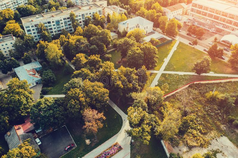 Aerial view of city garden park with green grass and trees and pathways among streets and buildings in summer sunset stock images