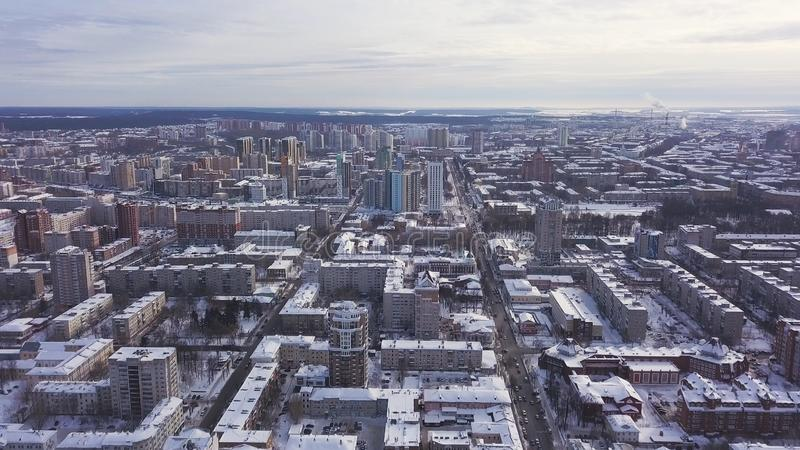 Aerial view of the city and many houses, roads, and yards in the winter time. Clip. Beautiful cityscape with different. Aerial view of the city and many houses royalty free stock images