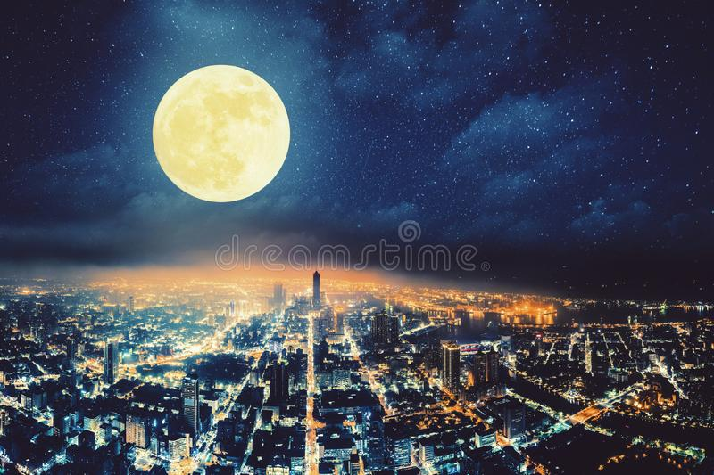 View of city at night with full moon. Aerial view of city at night with full moon royalty free stock photography