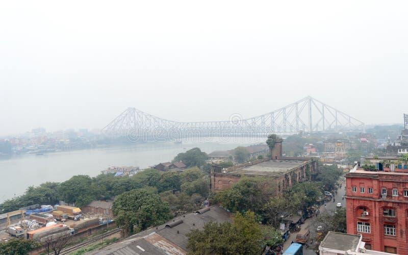 Aerial view Cityscape Howrah Bridge Rabindra Setu of Calcutta city life on Hooghly riverside near Burrabazar area on a foggy. Winter evening day. Kolkata West stock photography