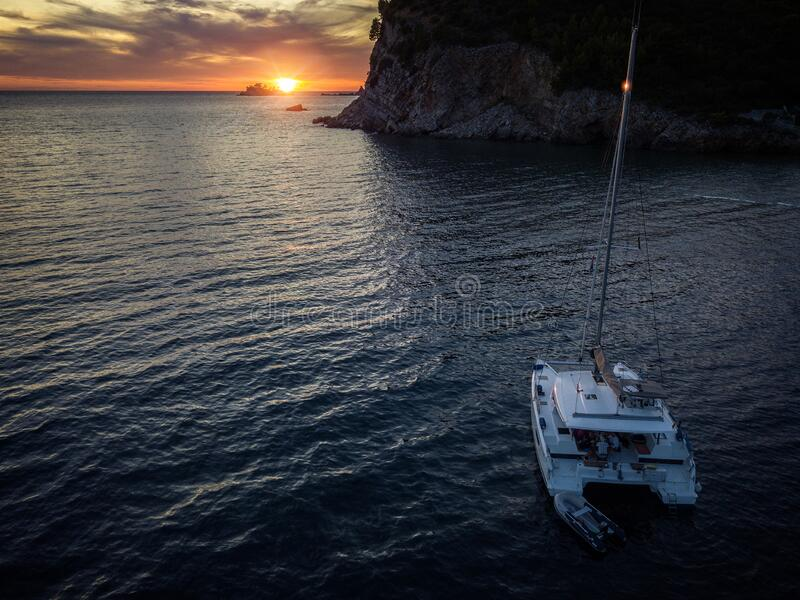 Aerial view of a cliff overlooking the sea and a catamaran moored at sunset, boat. Buljarica Beach. Montenegro royalty free stock image