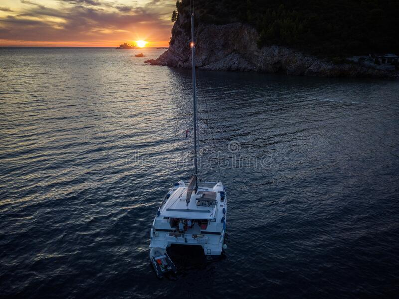 Aerial view of a cliff overlooking the sea and a catamaran moored at sunset, boat. Buljarica Beach. Montenegro stock images