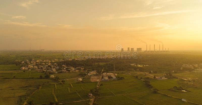 Aerial view of coal power plant - Sunrise near green agriculture field with factories outside the city, Raichur, India.  royalty free stock photography