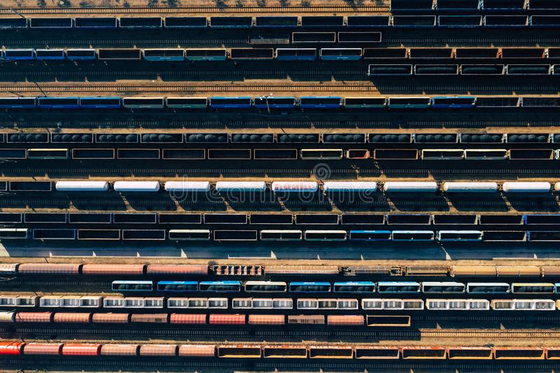 Aerial view of colorful freight trains on the railway station. Wagons with goods on railroad. Heavy industry. Industrial stock image