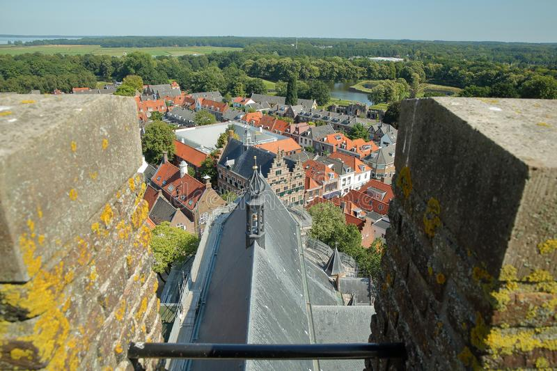 Aerial view of the colorful roofs and houses of Naarden, Netherlands. With the fortified walls of the Grote Kerk Church clock tower in the foreground royalty free stock image