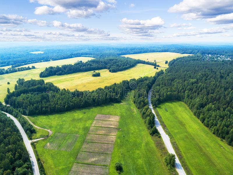 Aerial view of a country road in the forest with moving cars. Landscape. Captured from above with a drone. Aerial bird`s eye road stock photos