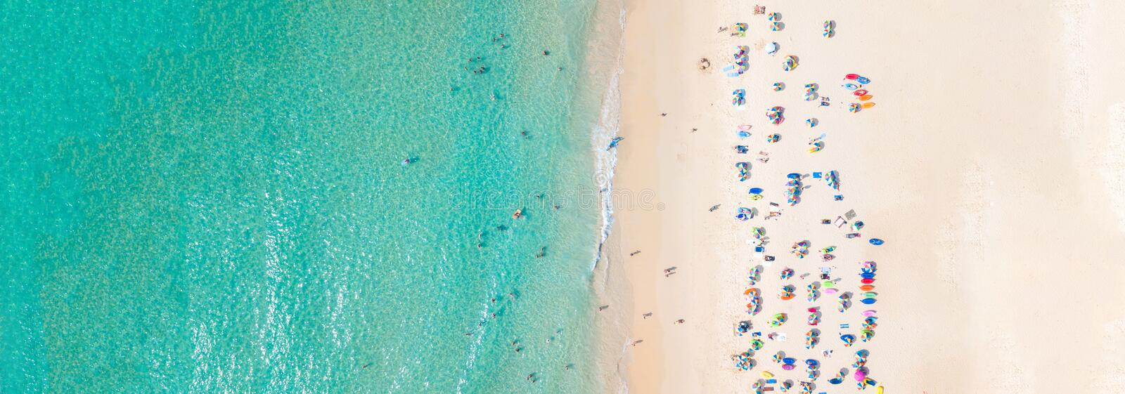 Aerial view crowded public beach with colourful umbrellas, Aerial view of sandy beach with tourists swimming in beautiful clear stock photography