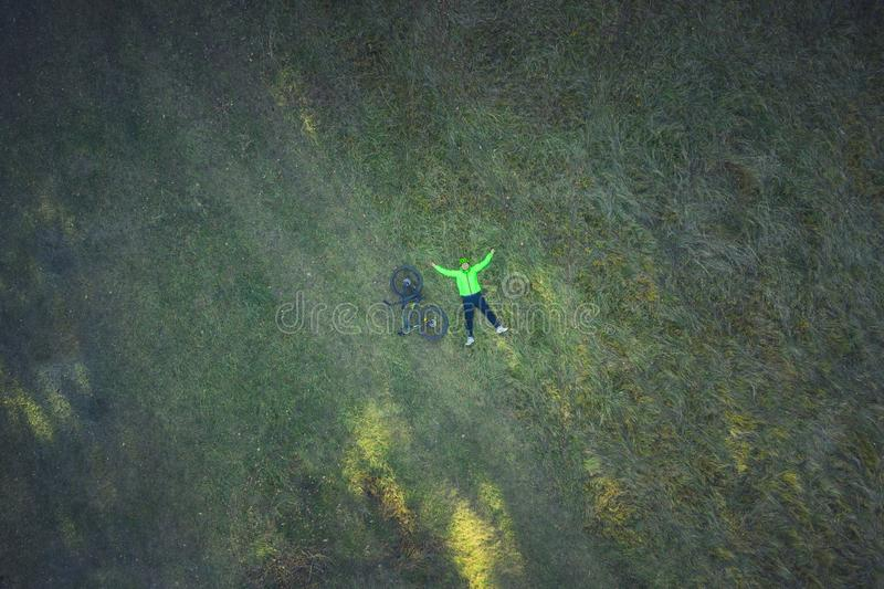 Aerial view of cyclist resting in meadow. Aerial drone view of a cyclist lying down and resting in a meadow stock photo