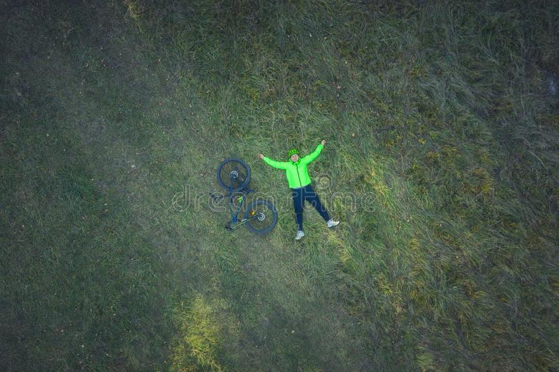 Aerial view of cyclist resting in meadow. Aerial drone view of a cyclist lying down and resting in a meadow royalty free stock photo