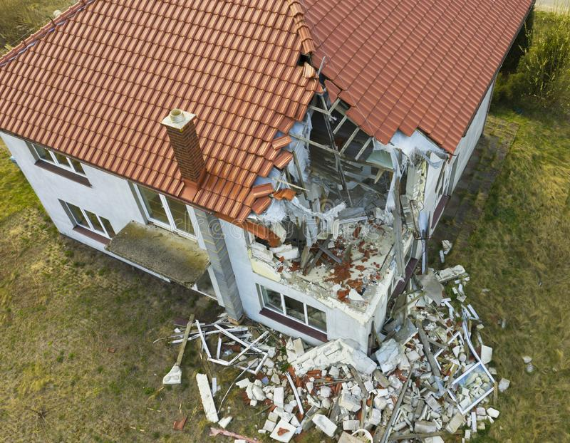 Aerial view on damaged red single house roof after strong wind or explosion. Hole in the rooftop and floor. Rubble on the ground royalty free stock photos