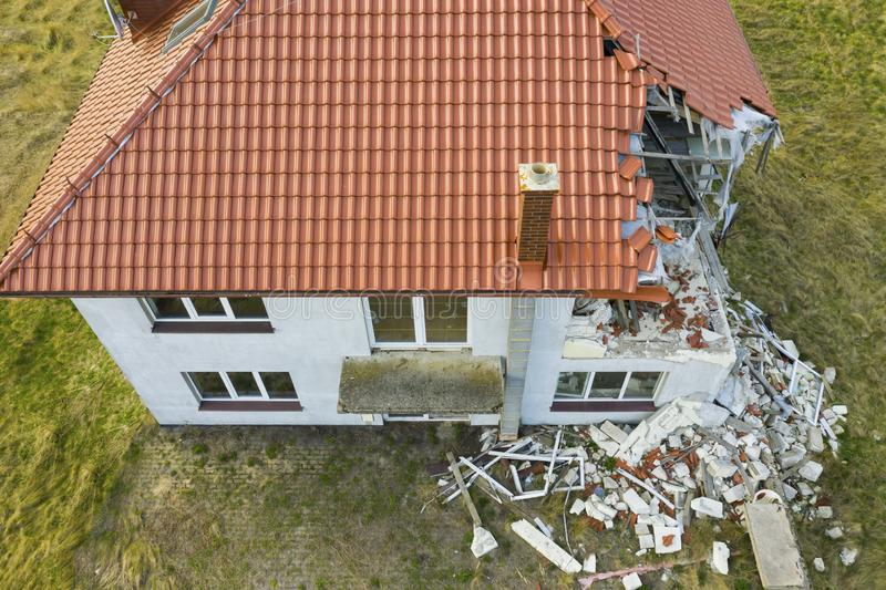 Aerial view on damaged red single house roof after strong wind or explosion. Hole in the rooftop and floor. Rubble on the ground stock images