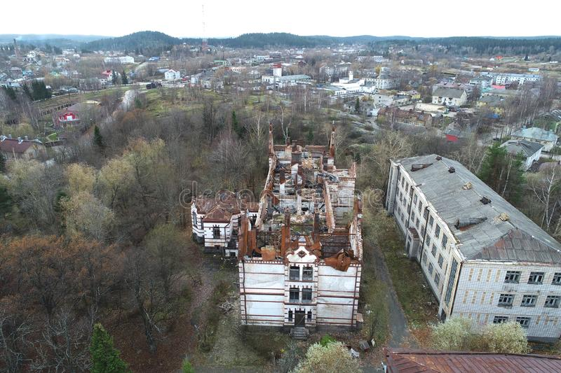 Aerial view on damaged red single house roof after strong wind or explosion. Hole in the rooftop and floor. Rubble on the ground royalty free stock images