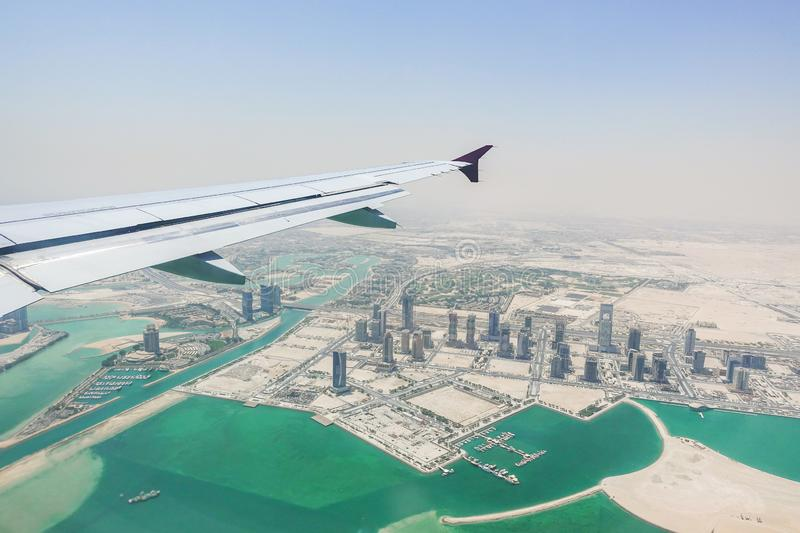 Aerial view of Doha, Qatar taken from airplane window with wing royalty free stock photography