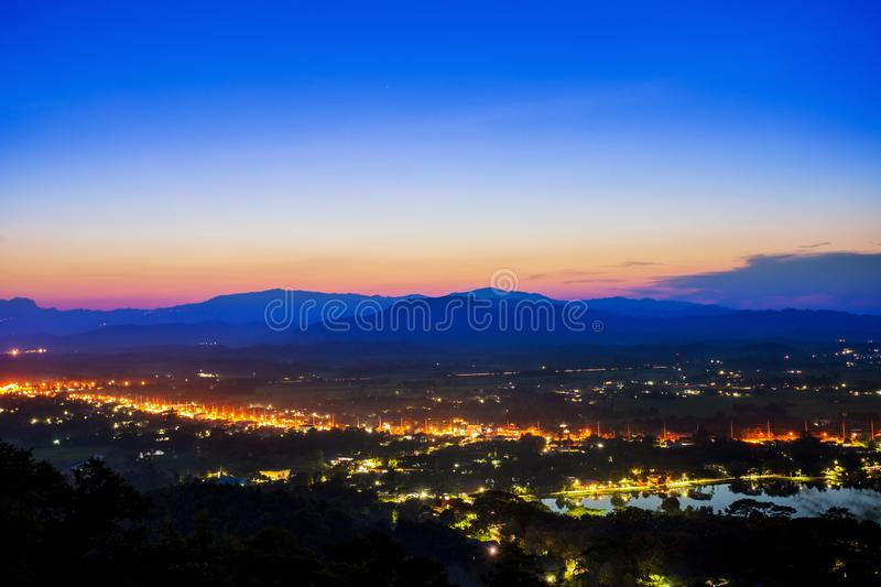 Aerial view at Doi Khao Kwai during blue zone after sunset. Mountain range as background with light tail on main road at Chiangrai. City and big pond as royalty free stock photography