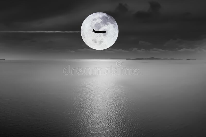 Aerial view Dramatic atmosphere black and white image of super full moon with silhouette aircraft fly over on peaceful ocean and. Dark sky background royalty free stock image
