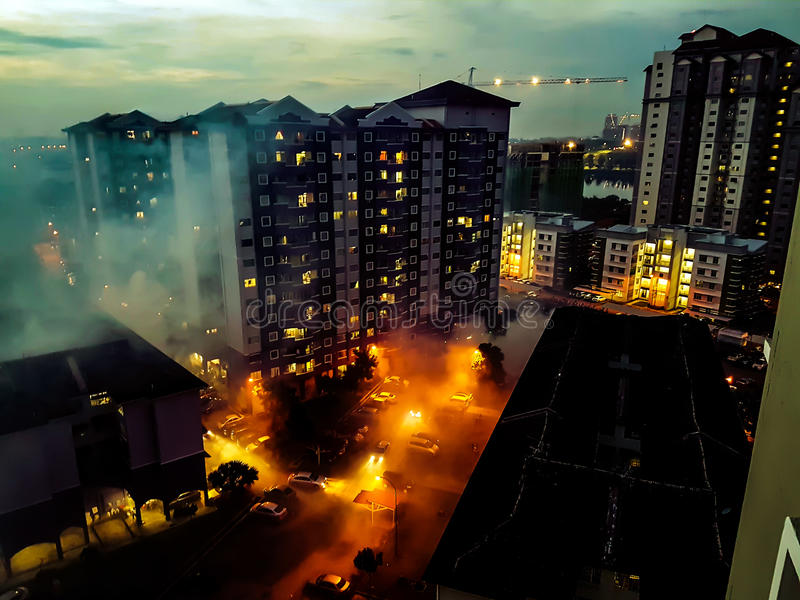 Aerial view of dramatic scene below which looked like buildings are on fire due to lights reflected on foggy evening. royalty free stock photography