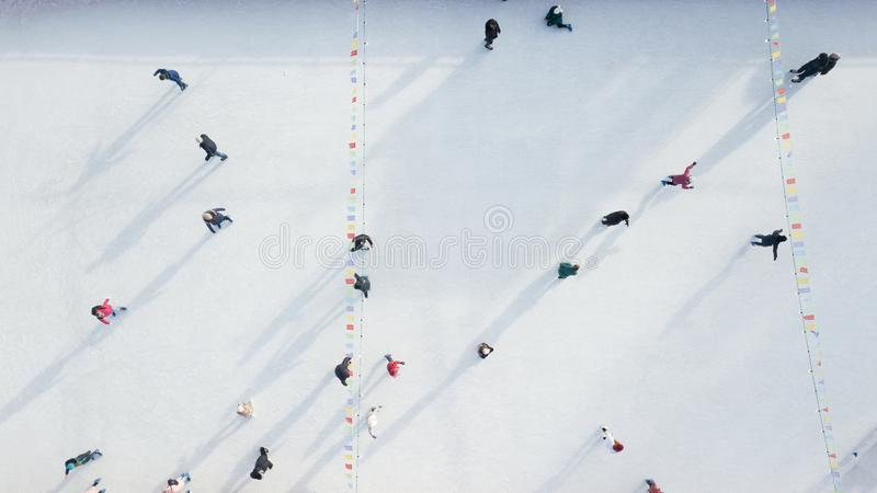 Aerial view of a drone on an open ice rink with people on a winter sunny day. stock photo