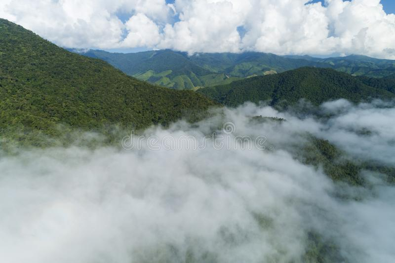 Aerial view drone shot of flowing fog waves on mountain tropical rainforest,Bird eye view image over the clouds Amazing nature royalty free stock photo