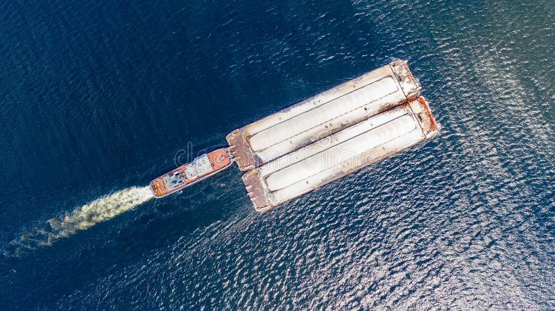 Aerial view from the drone of a small ship pushes a barge on the Volga river.  stock photos