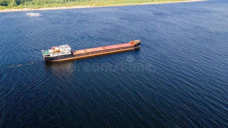 Aerial view from the drone of a small ship pushes a barge on the Volga river.  stock photography