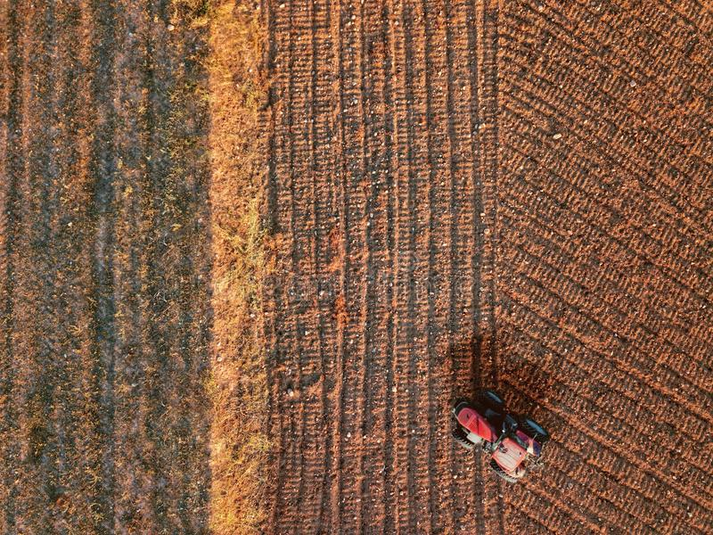 Aerial view from a drone of a tractor while tillage and ploughing in a farm land field. Top view for agriculture concept. And empty copy space for Editor`s text royalty free stock photos