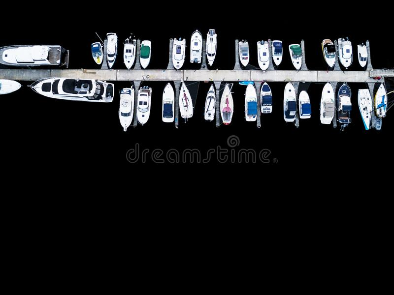 Aerial View by Drone of Yacht Club and Marina. Top view of yacht club. White boats in sea water. Marina dock yachts and small moto. R boats. Yacht and sailboat stock photos