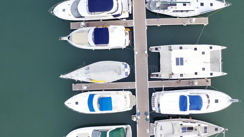 Aerial View by Drone of Yacht Club and Marina. Top view of yacht club. White boats in sea water. Marina dock yachts and stock photos