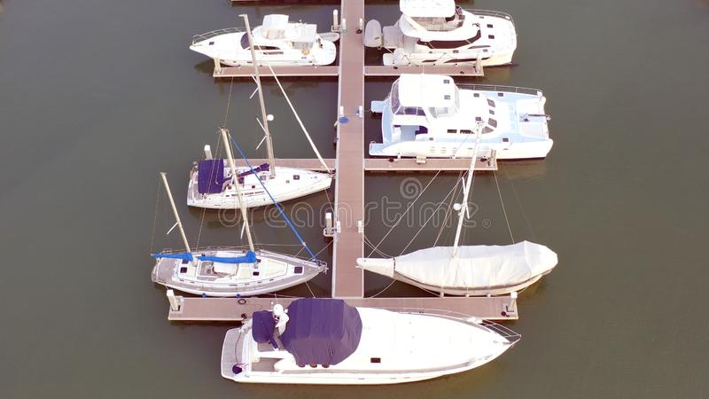 Aerial View by Drone of Yacht Club and Marina. Top view of yacht club. White boats in sea water. Marina dock yachts and stock photography
