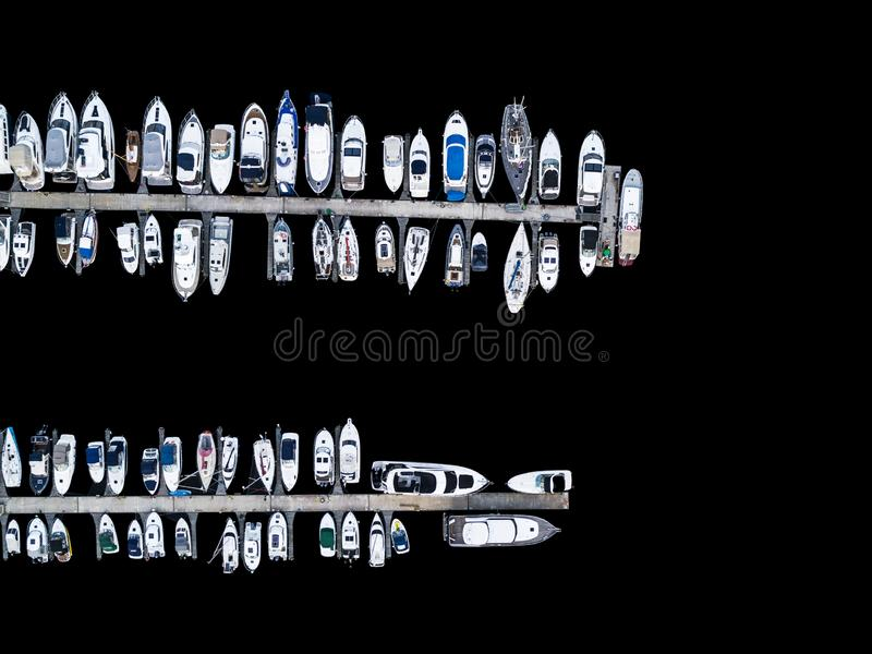 Aerial View by Drone of Yacht Club and Marina. Top view of yacht club. White boats in sea water. Marina dock yachts and small moto. R boats. Yacht and sailboat royalty free stock image